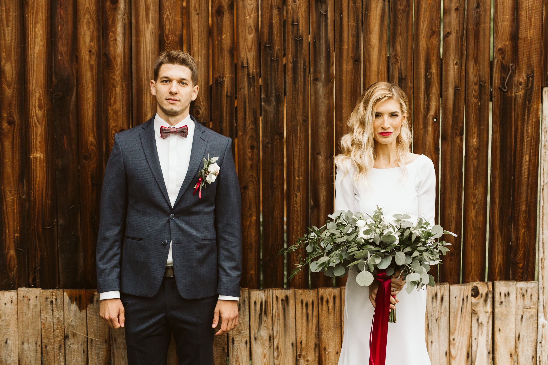 Groom and bride standing in front of barn