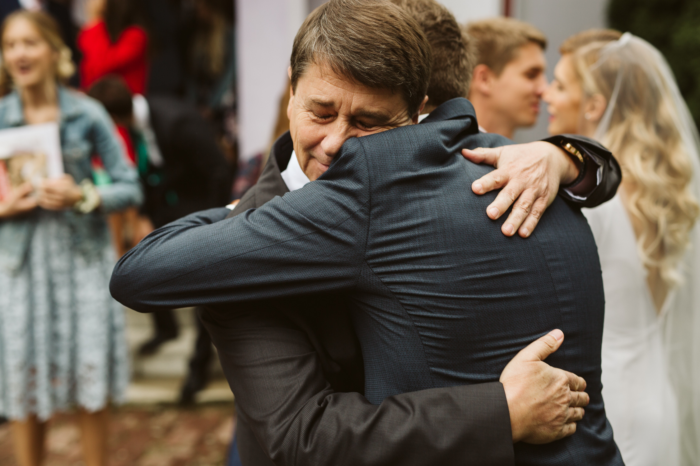 son hugging his father in front of church